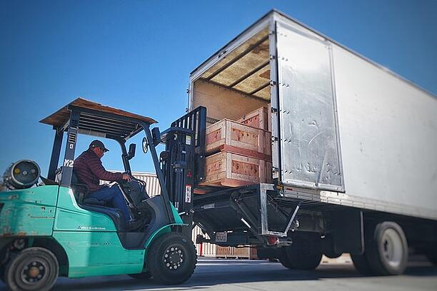 Loading wooden crates in truck with forklift.jpg